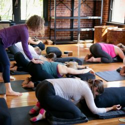 Carol Gray Helps Her Students With Child's Pose at MamaSpace Yoga